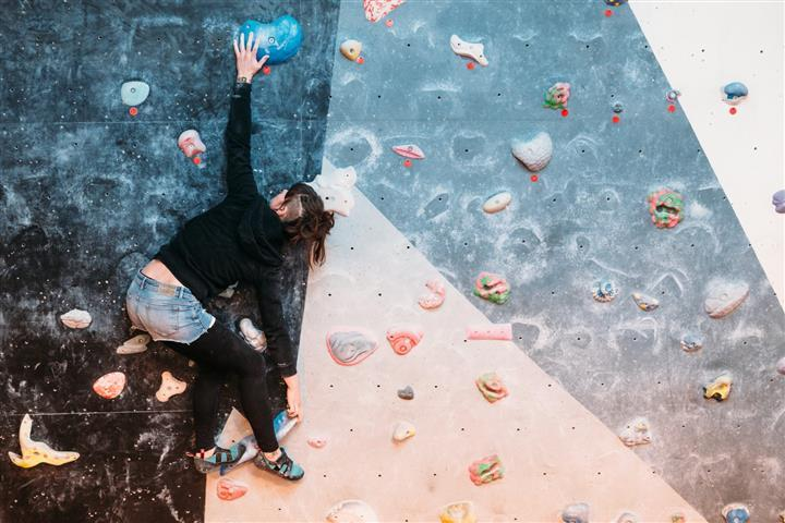 climber stretching on the wall in an awkward position
